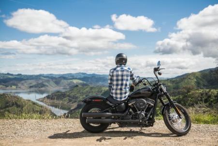 Ein Motorrad-Fahrer sitzt auf seiner Maschine und blickt in ein Tal